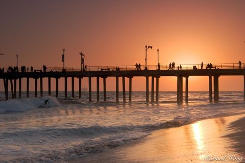 Surfer Riding Wave at Sunset Next to Huntington Beach Pier, California, photo