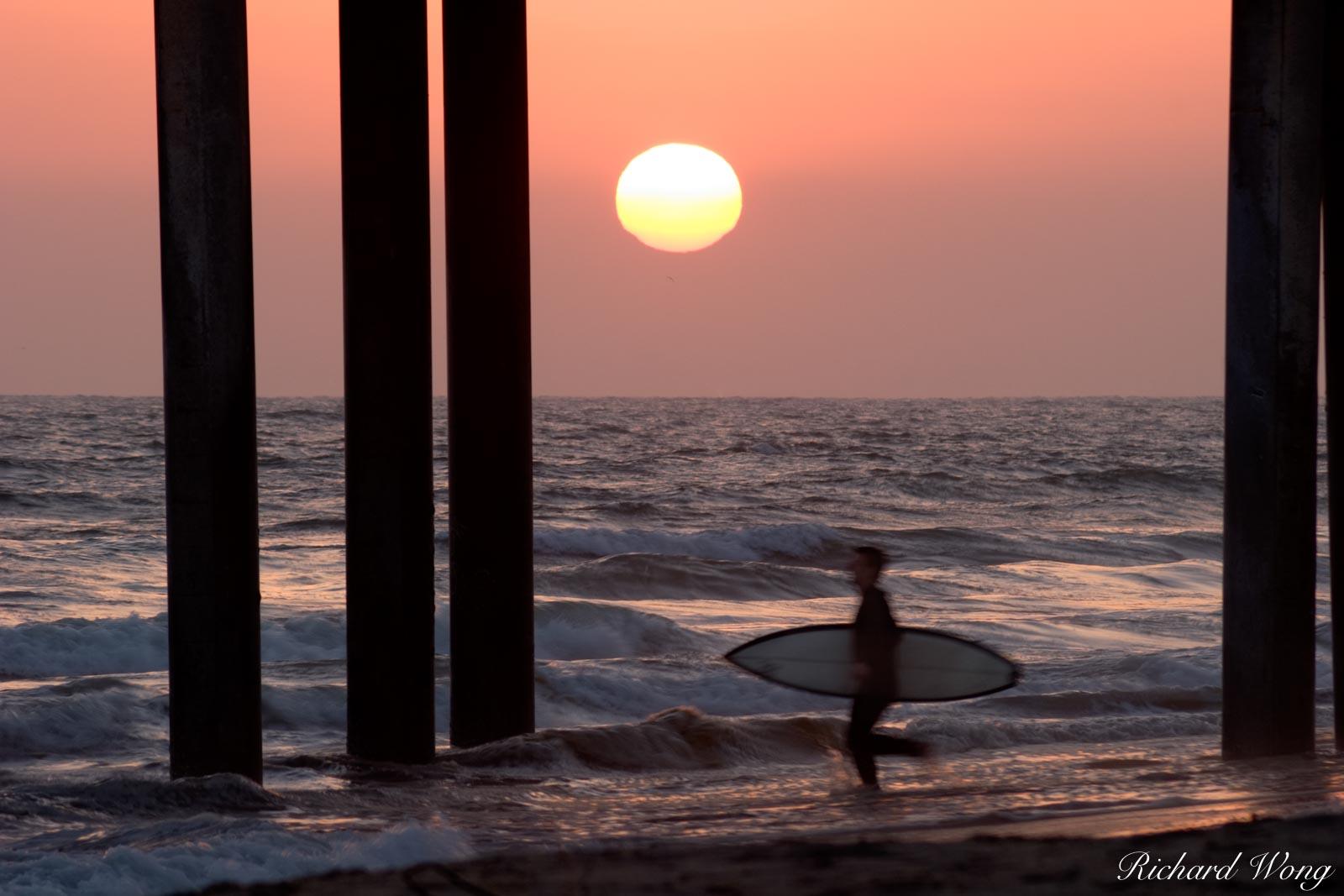 Surfer Running into Surf at Sunset Under Huntington Beach Pier, California, photo